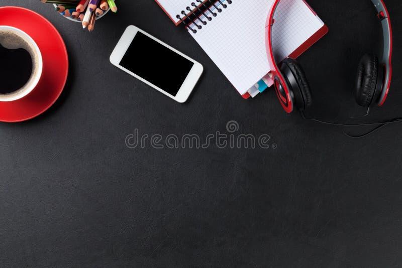 Γραφείο με το σημειωματάριο, τον καφέ, το smartphone και τα ακουστικά στοκ εικόνες