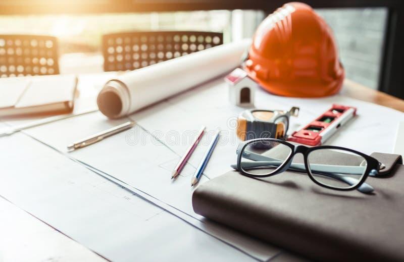 Γραφείο του μηχανικού σπιτιών αρχιτεκτόνων που στηρίζεται ένα σχεδιάγραμμα στην εργασία στοκ εικόνες