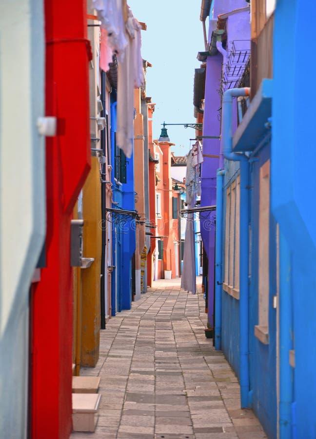 Γραφικά πολύ στενά οδός και προαύλιο νησιών Burano με τα μικρά ζωηρόχρωμα σπίτια στη σειρά ενάντια στο νεφελώδη μπλε ουρανό, Βενε στοκ εικόνα με δικαίωμα ελεύθερης χρήσης