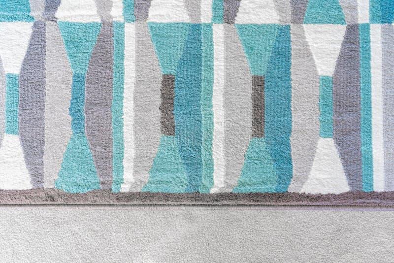 Γραφική, τοπ άποψη υποβάθρου μιας γεωμετρικής κουβέρτας με τα μπλε και γκρίζα σχέδια χρώματος, πάνω από έναν μπεζ τάπητα, ως στοι στοκ εικόνες