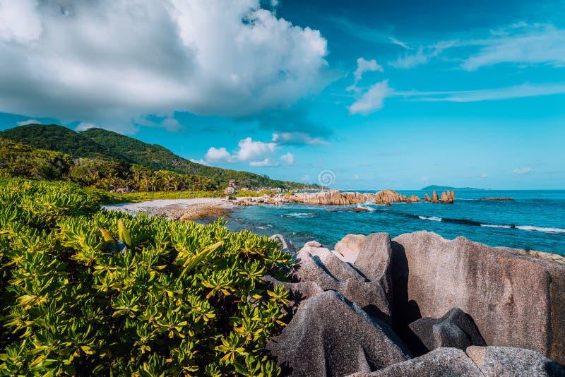 Γραφική τροπική ακτή με την κρυμμένη παραλία με τους μοναδικούς μεγάλους βράχους γρανίτη, το πολύβλαστο φύλλωμα και μερικά σύννεφ στοκ φωτογραφίες