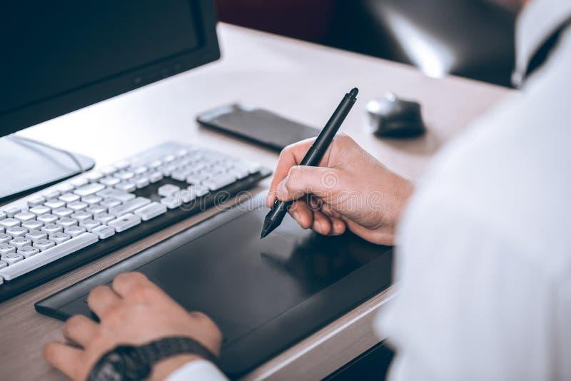 Γραφικός χώρος εργασίας σχεδιαστών ` s Χέρι στην ταμπλέτα μανδρών Νέο έξυπνο άτομο στο γραφείο Ελεύθερο μαύρο διάστημα αντιγράφων στοκ εικόνες