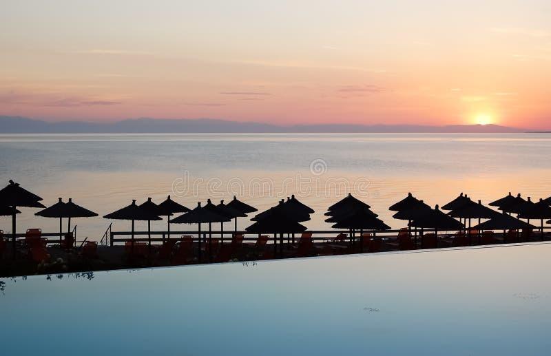 Γραφικό ηλιοβασίλεμα, μπλε λίμνη και παραλία με τις ομπρέλες στην Ελλάδα στοκ εικόνες