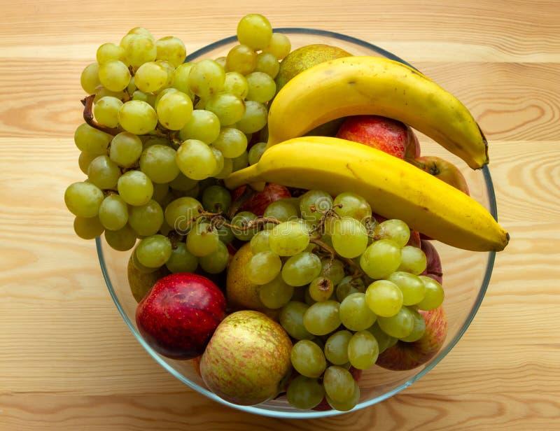 Γυαλί γύρω από το πιάτο βάζων των φρούτων, μπανάνες, σταφύλια, μήλα, αχλάδια στοκ φωτογραφίες