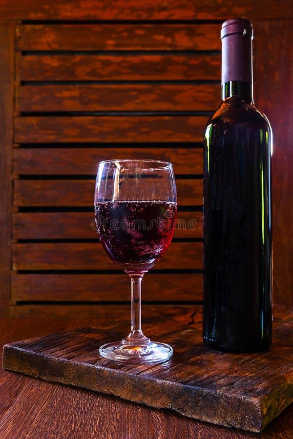 Γυαλί κρασιού και μπουκάλι κρασιού στον ξύλινο πίνακα στοκ φωτογραφία με δικαίωμα ελεύθερης χρήσης