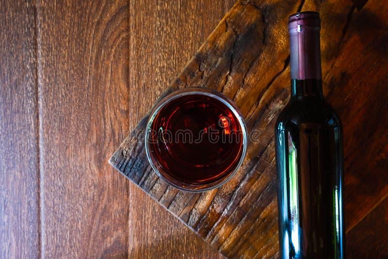 Γυαλί κρασιού και μπουκάλι κρασιού στον ξύλινο πίνακα στοκ εικόνα