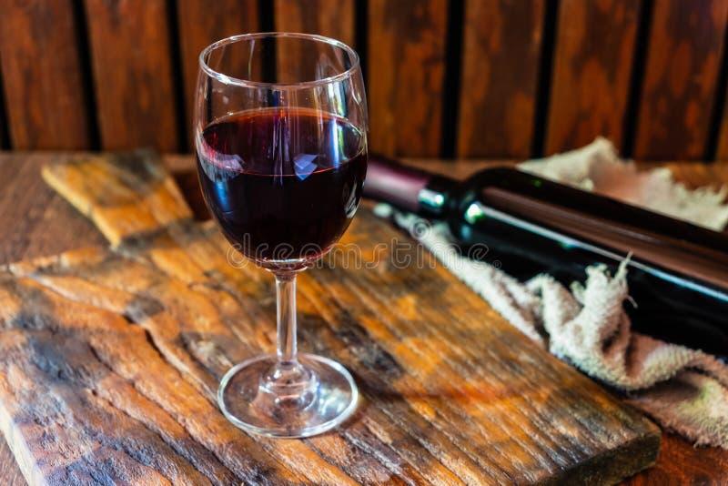 Γυαλί κρασιού και μπουκάλι κρασιού στον ξύλινο πίνακα στοκ εικόνες