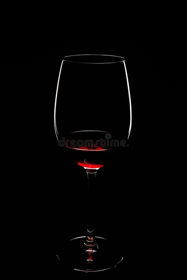 Γυαλί κρασιού με το κόκκινο κρασί στο μαύρο υπόβαθρο στοκ εικόνες