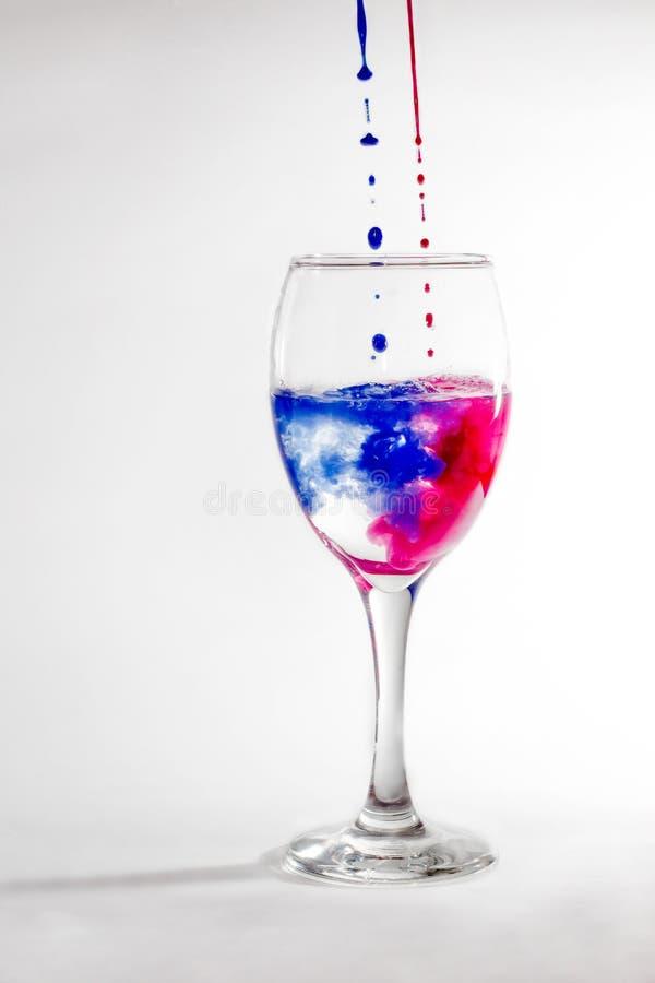 Γυαλί κρασιού με το νερό και τα χρώματα στοκ εικόνα με δικαίωμα ελεύθερης χρήσης