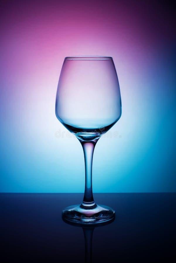 Γυαλί κρασιού σε ένα πορφυρό άσπρο μπλε υπόβαθρο στοκ εικόνες