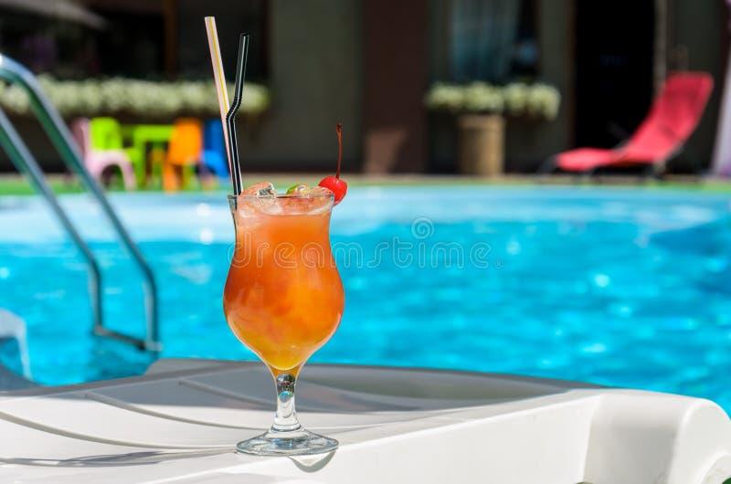 Γυαλί με ένα πορτοκαλί ποτό στην άκρη μιας μπλε λίμνης στοκ εικόνα