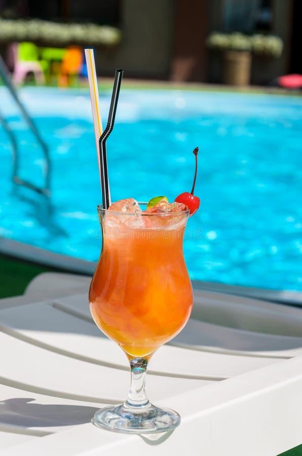 Γυαλί με ένα πορτοκαλί ποτό στην άκρη μιας μπλε λίμνης στοκ φωτογραφία με δικαίωμα ελεύθερης χρήσης