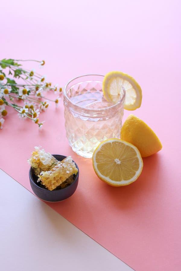 Γυαλί με τη χειροποίητη λεμονάδα, τις χτένες μελιού, τα λουλούδια και τα λεμόνια στο κοράλλι/το ρόδινο υπόβαθρο στοκ εικόνες με δικαίωμα ελεύθερης χρήσης