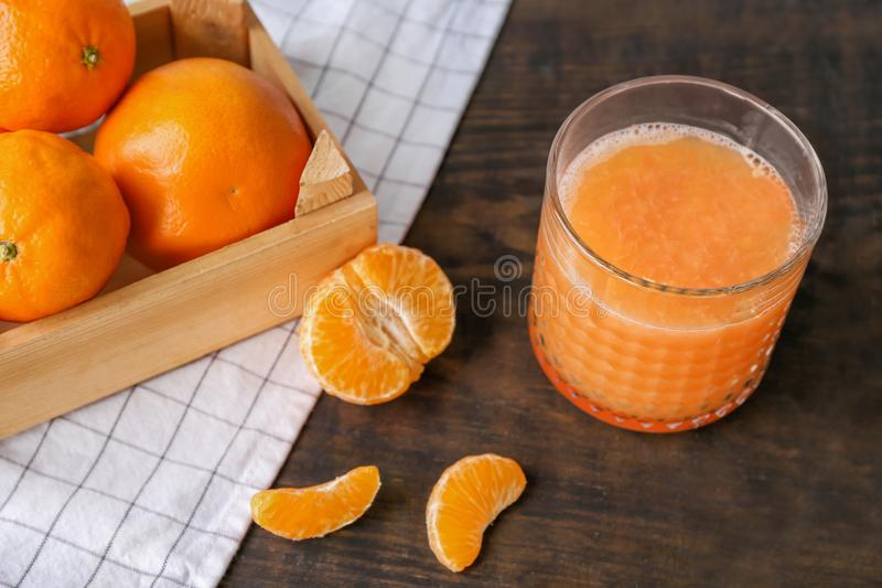 Γυαλί με τον εύγευστο χυμό εσπεριδοειδών και φρέσκα tangerines στον πίνακα στοκ φωτογραφία
