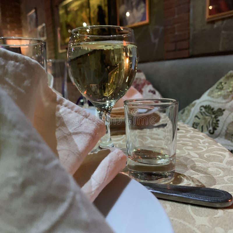 Γυαλί με το άσπρο κρασί στον πίνακα στο εστιατόριο στοκ φωτογραφία με δικαίωμα ελεύθερης χρήσης