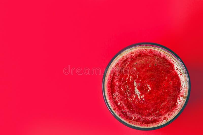 Γυαλί με το καταφερτζή μούρων και φρούτων κόκκινων τεύτλων από τα μήλα μπανανών σταφίδων σμέουρων φραουλών στο ίδιο υπόβαθρο χρώμ στοκ φωτογραφία