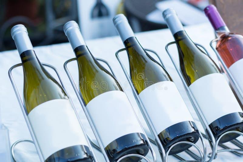 Γυαλί μπουκαλιών με το άσπρο κρασί στη σειρά στον πίνακα στοκ φωτογραφίες