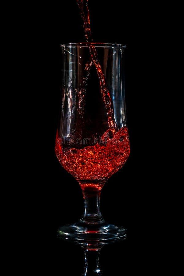 γυαλί που χύνει το κόκκιν& στοκ φωτογραφία με δικαίωμα ελεύθερης χρήσης