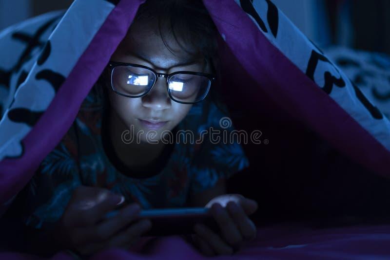 Γυαλιά ένδυσης κοριτσιών που χρησιμοποιούν το κινητό τηλέφωνο στο σκοτάδι στοκ φωτογραφία