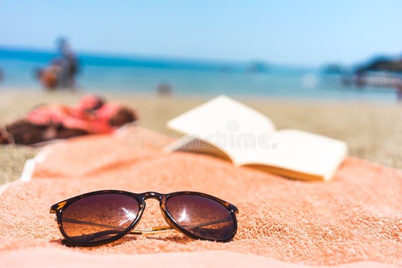 Γυαλιά ηλίου και βιβλίο σε μια πετσέτα στην παραλία στοκ φωτογραφία