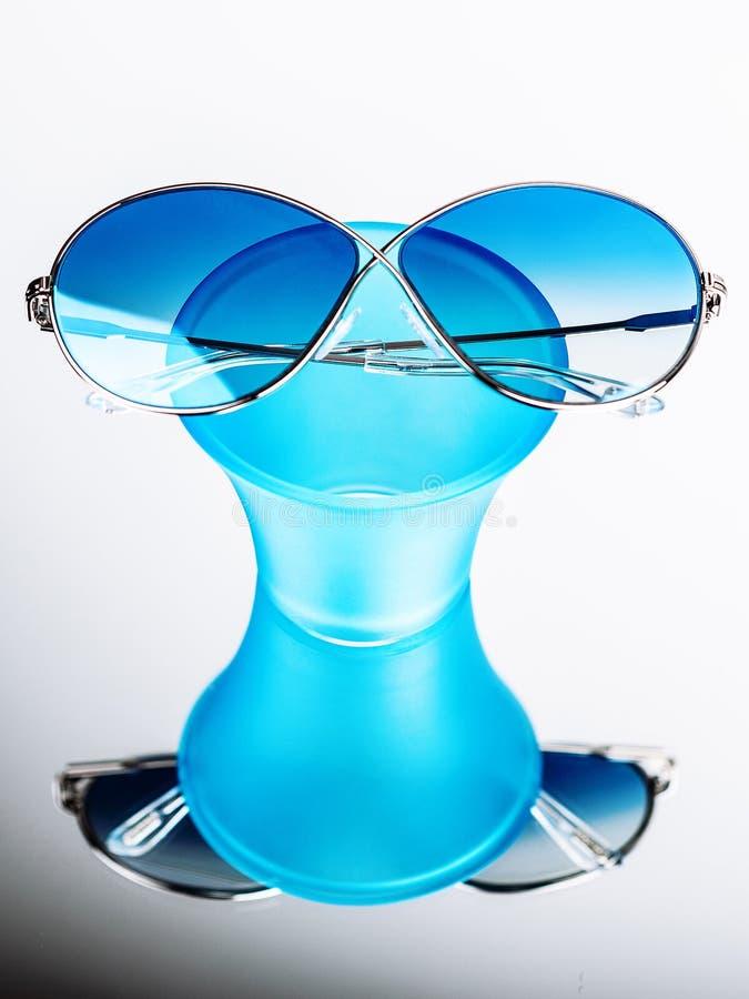 Γυαλιά ηλίου με τα μπλε γυαλιά σε μια μπλε στάση στοκ εικόνα με δικαίωμα ελεύθερης χρήσης