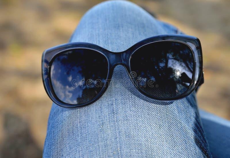 Γυαλιά ηλίου που φοριούνται στο γόνατο στα τζιν, έννοια στοκ εικόνες