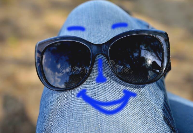 Γυαλιά ηλίου που φοριούνται στο γόνατο στα τζιν και ένα αστείο χρωματισμένο πρόσωπο, έννοια στοκ εικόνα με δικαίωμα ελεύθερης χρήσης