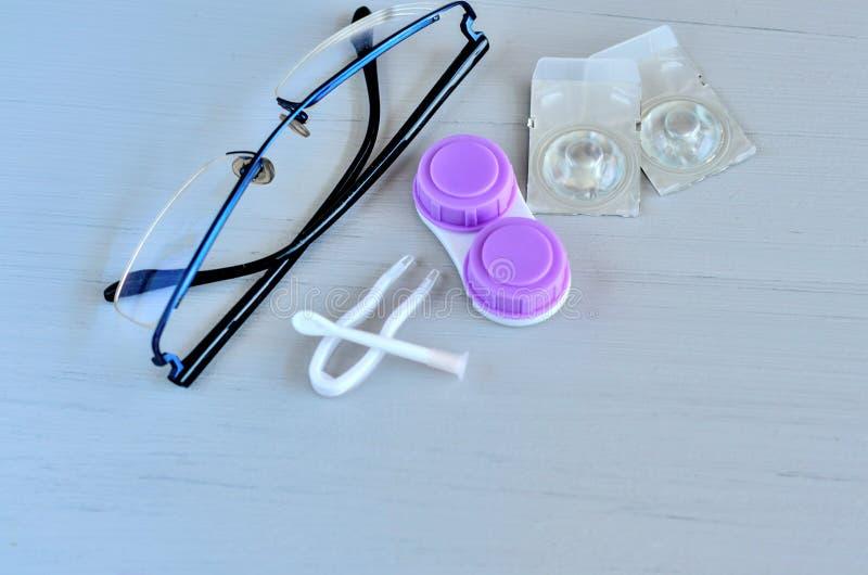 Γυαλιά και εξαρτήματα φακών επαφής στο γκρίζο υπόβαθρο στοκ φωτογραφία με δικαίωμα ελεύθερης χρήσης