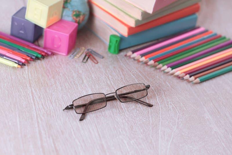 Γυαλιά και σχολικές προμήθειες στο ξύλινο υπόβαθρο φωτογραφία με το αντίγραφο στοκ εικόνα
