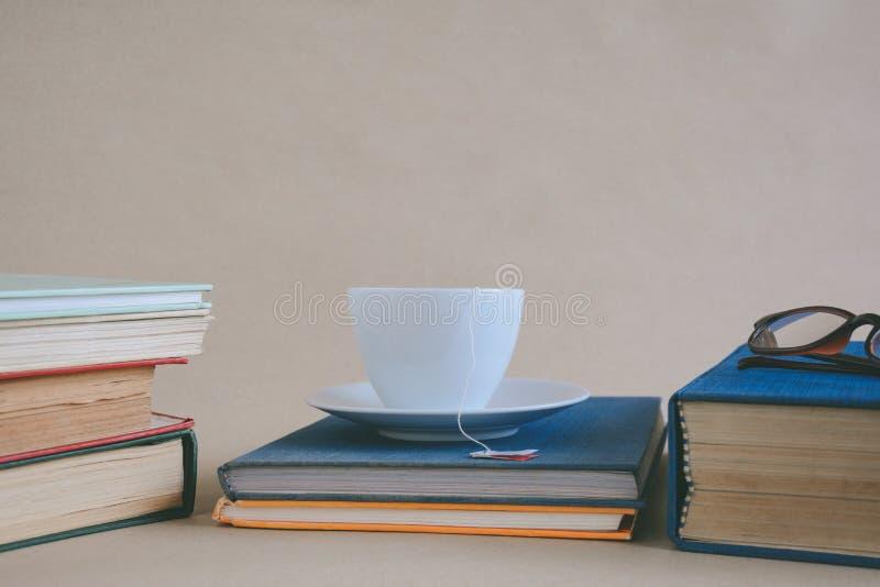 Γυαλιά και τσάι βιβλίων στο γραφείο με τη μελέτη και την εκπαίδευση concep στοκ εικόνα