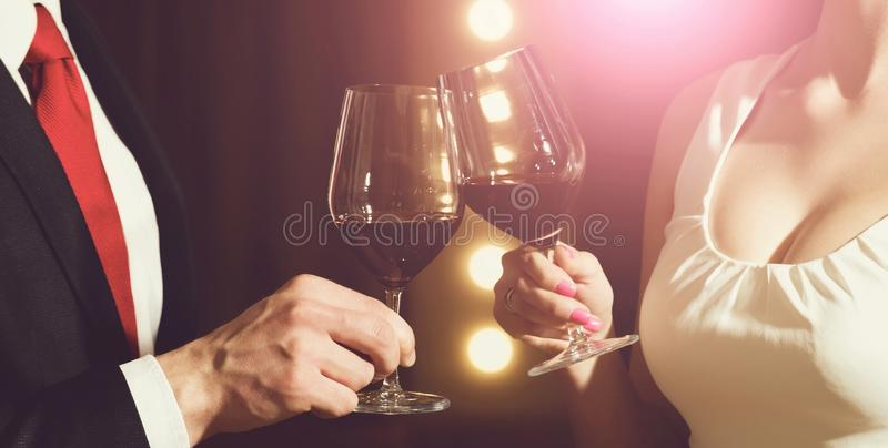 Γυαλιά κουδουνίσματος ζεύγους με το κόκκινο κρασί στη συνεδρίαση ή το γάμο στοκ φωτογραφία με δικαίωμα ελεύθερης χρήσης