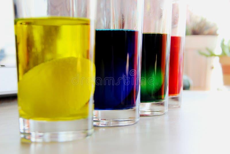 Γυαλιά με αυγά σε πολύχρωμο χρωματιστό νερό αυγό σε ποτήρι με κίτρινη χρωστική Πασχαλινά παρασκευάσματα στοκ φωτογραφίες με δικαίωμα ελεύθερης χρήσης