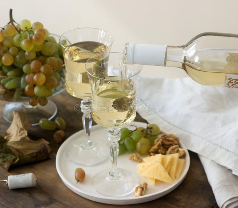 Γυαλιά με το άσπρο κρασί και ένα μπουκάλι του κρασιού με ένα πρόχειρο φαγητό - τυρί, ξύλα καρυδιάς και σταφύλια Αγροτικό ύφος στοκ εικόνα