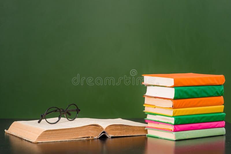 Γυαλιά που βρίσκονται στο βιβλίο κοντά στον κενό πράσινο πίνακα κιμωλίας στοκ εικόνες