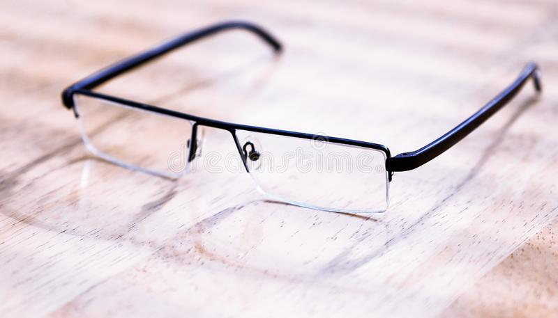 Γυαλιά στο μαύρο πλαίσιο στο ξύλινο υπόβαθρο, πίνακας κορυφαία όψη στοκ εικόνα