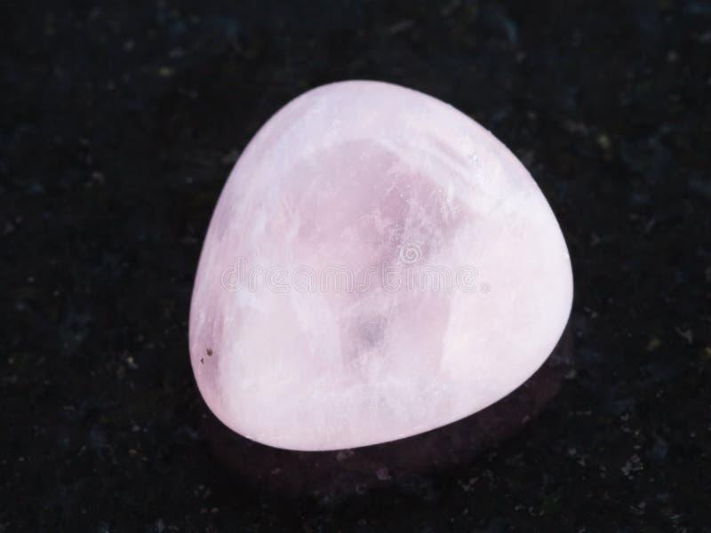 γυαλισμένη ρόδινη πέτρα πολύτιμων λίθων χαλαζία στο σκοτάδι στοκ εικόνα