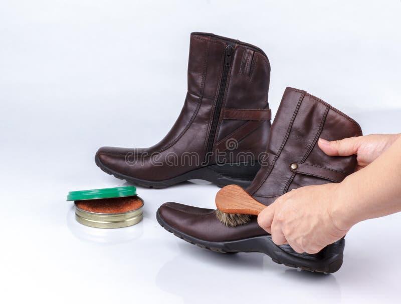 Γυαλίζοντας μπότα χεριών γυναίκας με τη βούρτσα παπουτσιών στοκ εικόνες