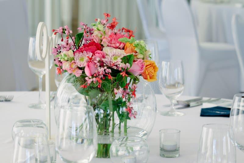 Γυαλί γύρω από το βάζο με τη φωτεινή ανθοδέσμη των λουλουδιών σε μια επιτραπέζια οργάνωση για το γεύμα στοκ εικόνα με δικαίωμα ελεύθερης χρήσης
