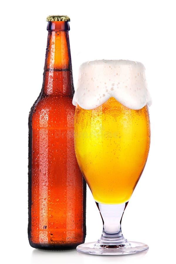 Γυαλί και μπουκάλι της μπύρας με τις πτώσεις που απομονώνονται στο λευκό στοκ εικόνα