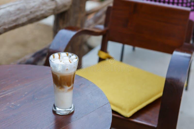 Γυαλί καφέ cappuccino καραμέλας στον πίνακα στον καφέ στοκ φωτογραφία με δικαίωμα ελεύθερης χρήσης