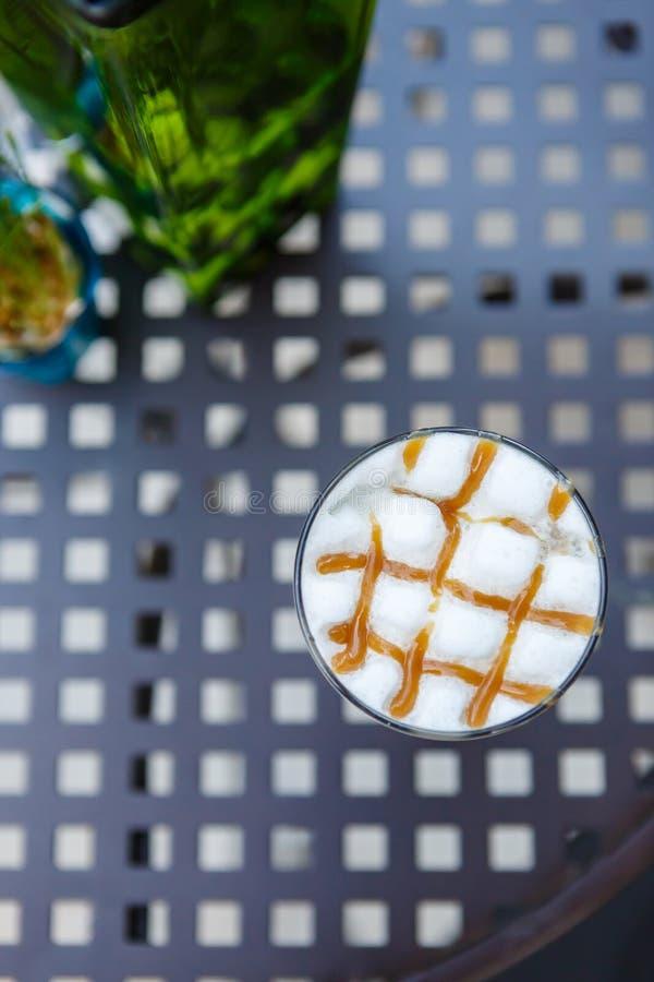 Γυαλί καφέ cappuccino καραμέλας στον πίνακα στον καφέ στοκ εικόνα με δικαίωμα ελεύθερης χρήσης