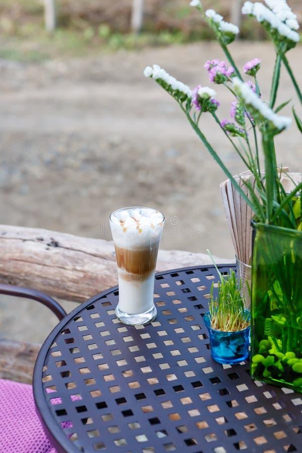 Γυαλί καφέ cappuccino καραμέλας στον πίνακα στον καφέ στοκ εικόνες