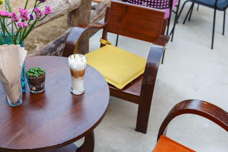 Γυαλί καφέ cappuccino καραμέλας στον πίνακα στον καφέ στοκ εικόνα