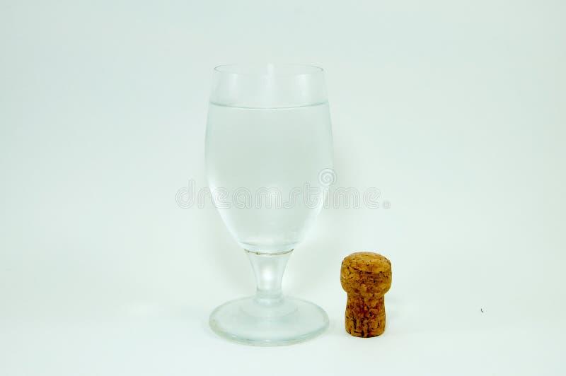 Γυαλί κρασιού και φελλός σαμπάνιας στο άσπρο υπόβαθρο στοκ εικόνα