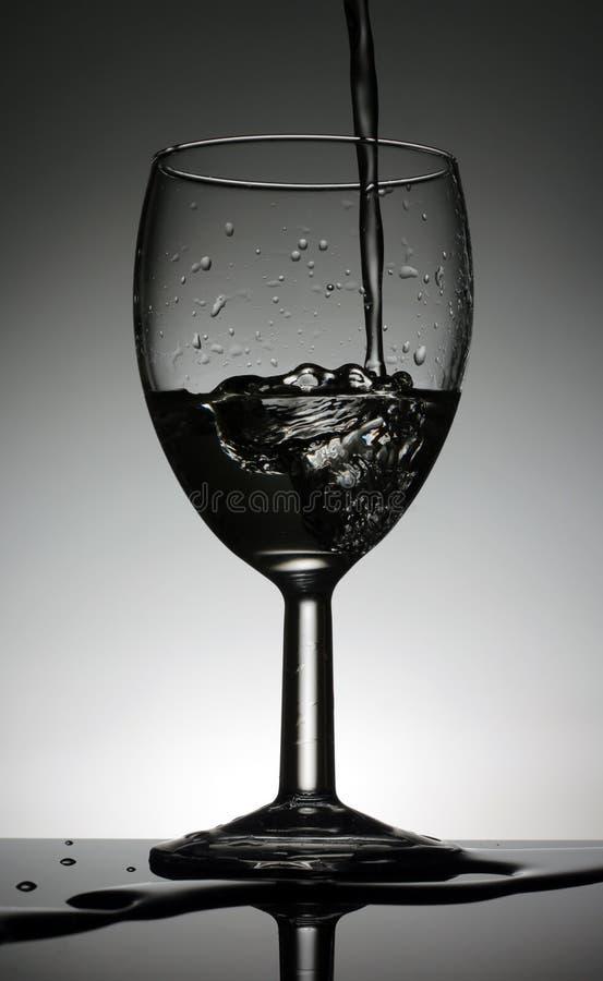 Γυαλί κρασιού με ένα χύνοντας νερό που στέκεται σε έναν μαύρο πίνακα στοκ φωτογραφία με δικαίωμα ελεύθερης χρήσης