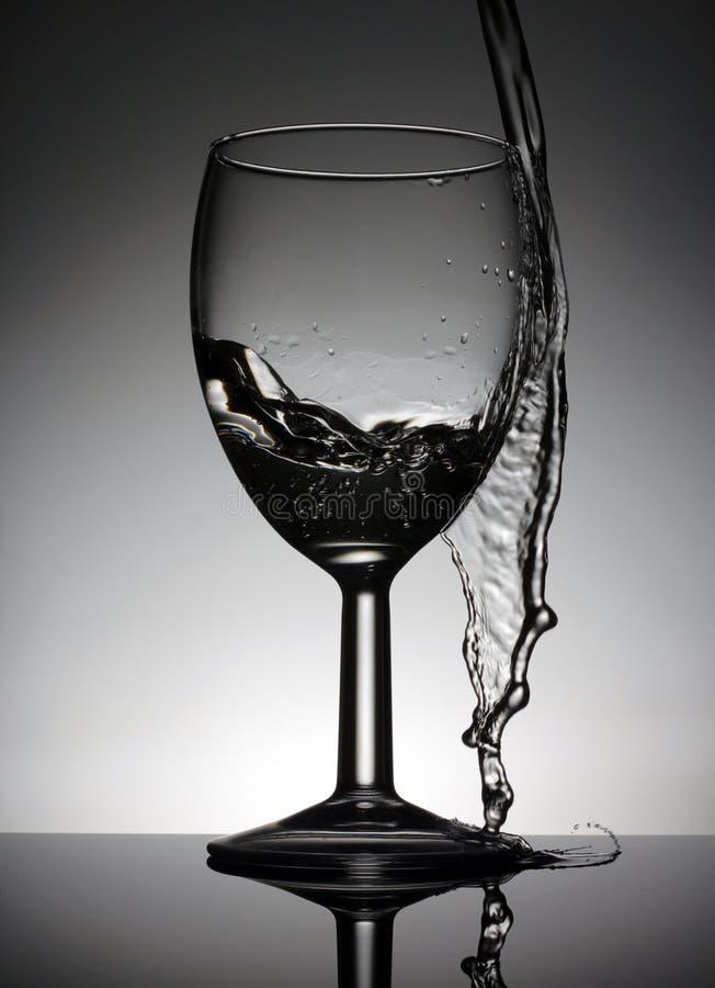 Γυαλί κρασιού με ένα χύνοντας νερό που στέκεται σε έναν μαύρο πίνακα στοκ φωτογραφίες με δικαίωμα ελεύθερης χρήσης