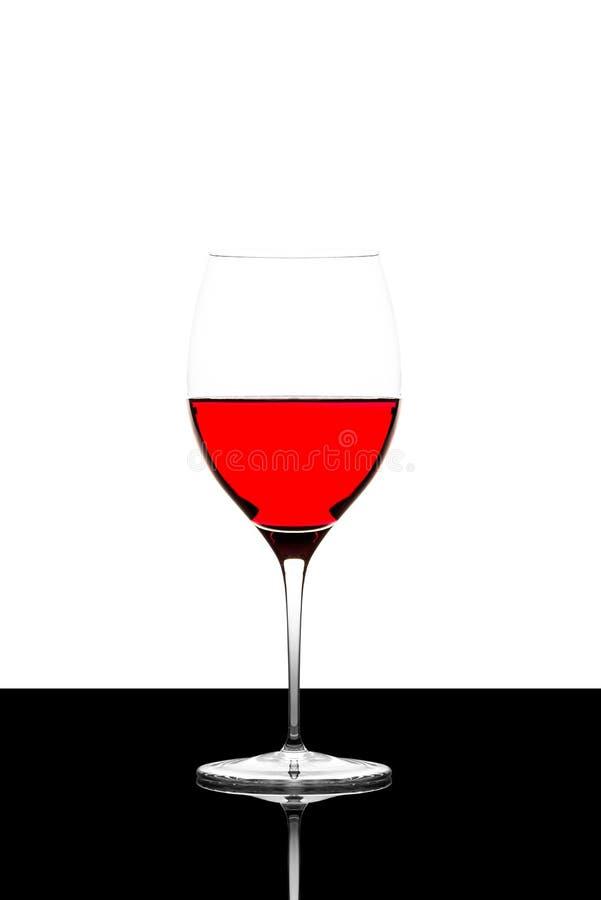 Γυαλί κόκκινου κρασιού σε έναν μαύρο πίνακα που απομονώνεται και αναδρομικά φωτισμένο στοκ φωτογραφία με δικαίωμα ελεύθερης χρήσης