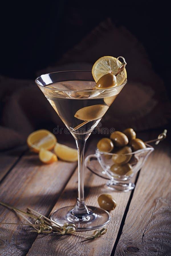 Γυαλί martini με τις πράσινες ελιές σε έναν παλαιό ξύλινο πίνακα στοκ εικόνες