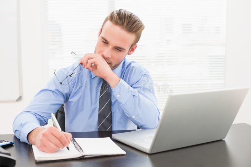 Γυαλιά εκμετάλλευσης επιχειρηματιών και λήψη των σημειώσεων στοκ εικόνες με δικαίωμα ελεύθερης χρήσης