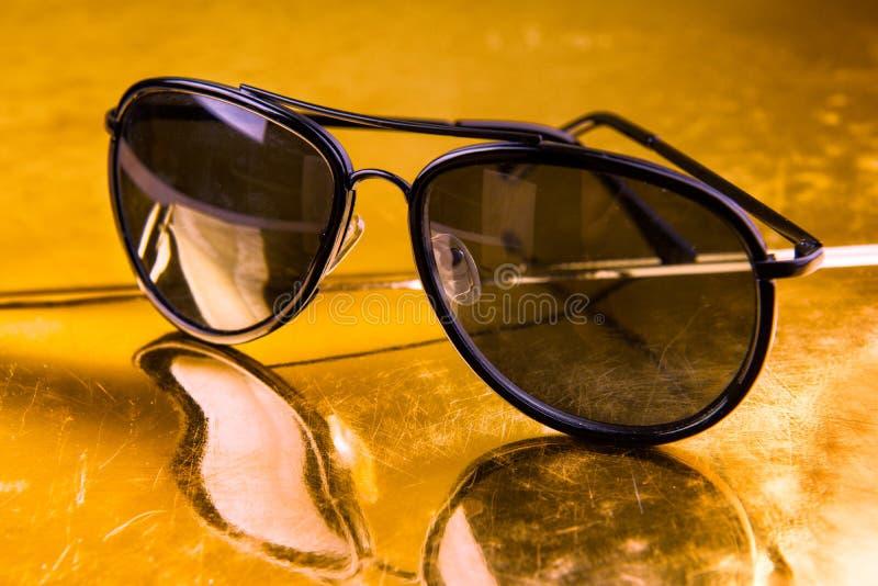 Γυαλιά ηλίου αεροπόρων πολυτέλειας στο χρυσό υπόβαθρο στοκ εικόνες